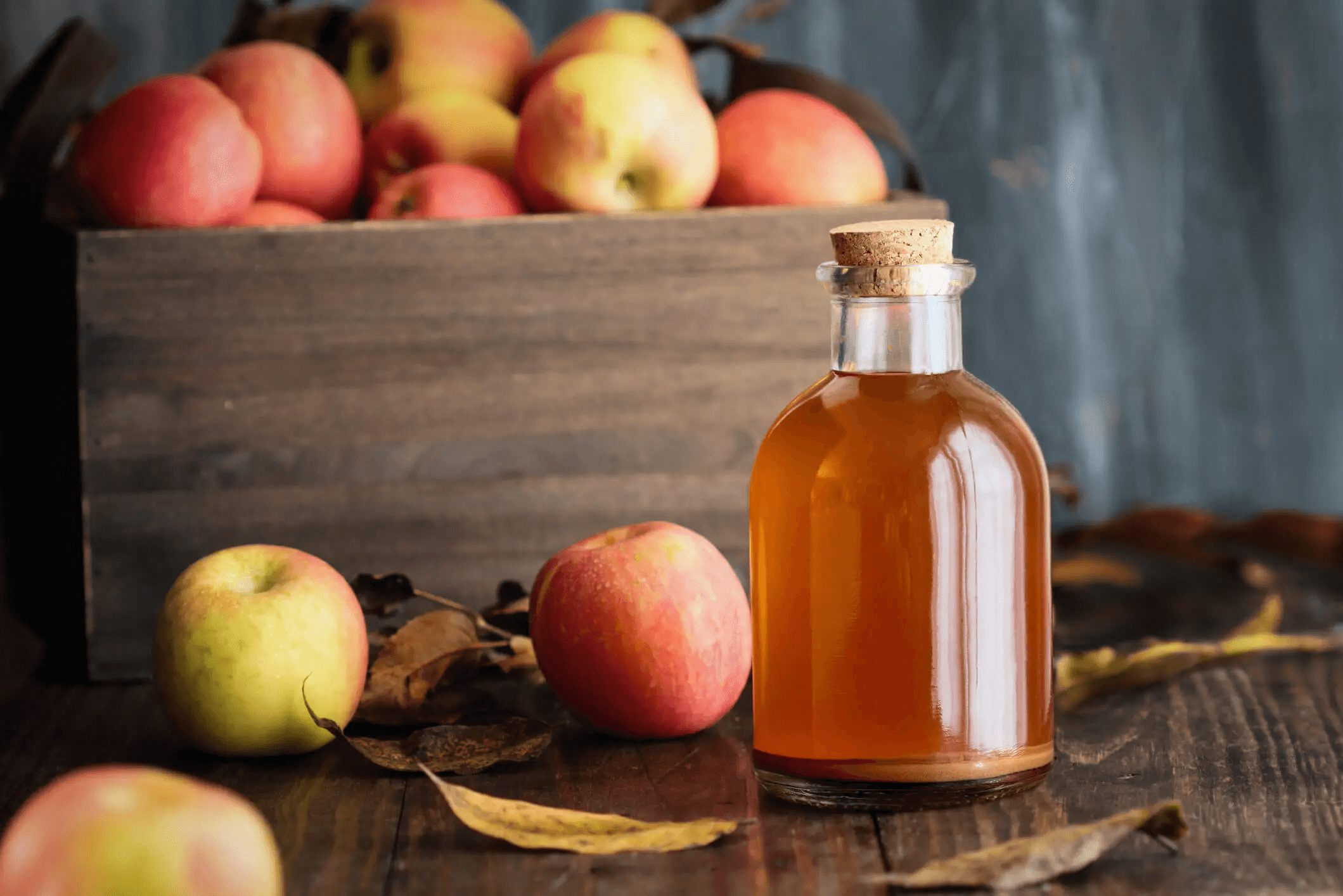 apple cider vinegar and crate of apples